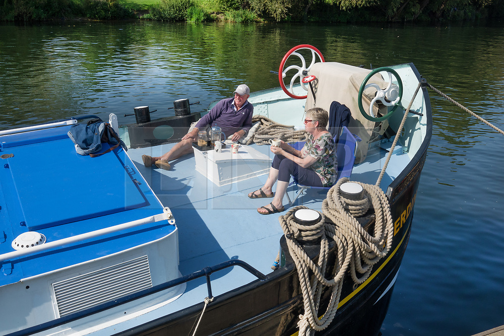 © Licensed to London News Pictures. 02/09/2017. Hampton Court, UK. A couple enjoy a cup of tea on the deck of their boat moored on the River Thames near Hampton Court. A period of warmer weather is predicted over the next few days after the recent wet spell. Photo credit: Peter Macdiarmid/LNP