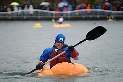 A man wearing a Captain America costume paddles a giant pumpkin across Lake of the Commons at the 14th annual West Coast Giant Pumpkin Regatta in Tualatin, Ore. on October 21, 2017. (Photo by Alex Milan Tracy)