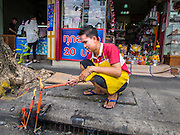 "10 AUGUST 2014 - BANGKOK, THAILAND: A man lights candles for Ghost Month in front of his shop in the Chinatown section of Bangkok. The seventh month of the Chinese Lunar calendar is called ""Ghost Month"" during which ghosts and spirits, including those of the deceased ancestors, come out from the lower realm. It is common for Chinese people to make merit during the month by burning ""hell money"" and presenting food to the ghosts.    PHOTO BY JACK KURTZ"