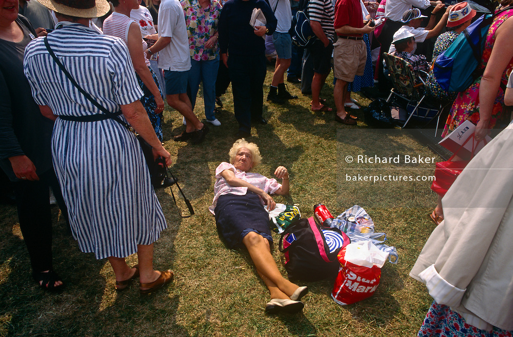 Elderly lady lies on grass surrounded by crowd, celebrating 50th anniversary of wartime VE Day when war in Europe was over.