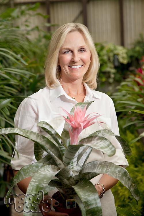 Portrait of a happy senior blond woman in botanical garden