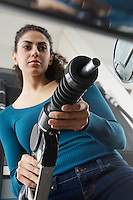 Woman holding fuel pump at gas station, tilt