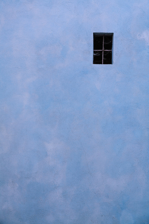 Blue stucco wall and barred window in Barola Italy alley
