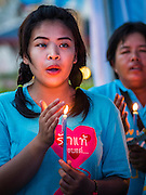 12 AUGUST 2015 - BANGKOK, THAILAND: Thais sing the Queen's Anthem during a candle light program in a park in Bangkok to honor Queen Sirikit of Thailand on her 83rd birthday. Queen Sirikit was born Mom Rajawongse Sirikit Kitiyakara on August 12, 1932. She is the queen consort of Bhumibol Adulyadej, King (Rama IX) of Thailand. She met Bhumibol in Paris, where her father was the Thai ambassador. They married in 1950, she was appointed Queen Regent in 1956. The King and Queen had one son and three daughters. She has not made any public appearances since her hospitalization in 2012. Her birthday is celebrated as Mother's Day in Thailand, schools and temples across Thailand hold ceremonies to honor the Queen and mothers.     PHOTO BY JACK KURTZ