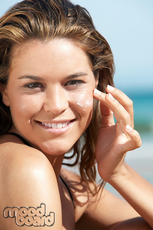 Young woman applying sunscreen to face on beach close-up