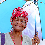 Cienfuegos, Cuba, woman walking during the mid-day with umbrella to protect her from the sun.