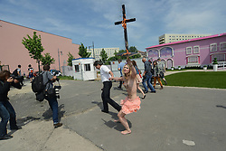 59653691 .A topless protester holds a burning crucifix during the Protest against the Opening of the controversial touring exhibition of Barbie in Berlin. Several Hundred Activists  demonstrate against the Role-image by Barbie by Women on Beauty Slenderness and Consumption, Berlin, Germany, May 16, 2013.   Photo by: imago / i-Images. UK ONLY