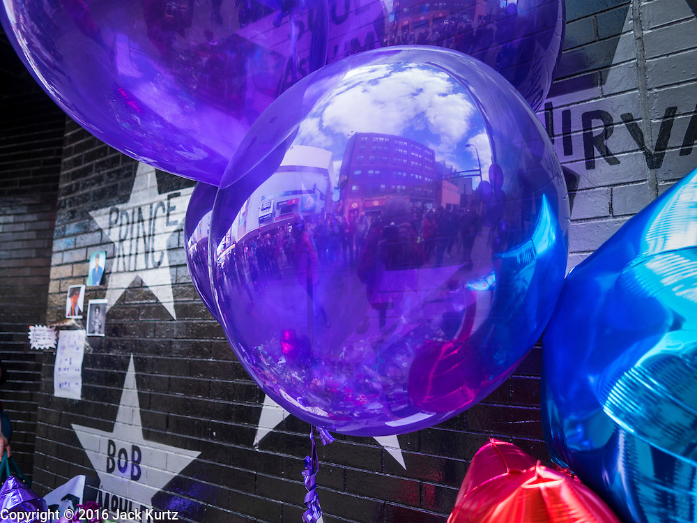 """22 APRIL 2016 - MINNEAPOLIS, MN: Purple balloons in front of Prince's star on the wall of 1st Ave in Minneapolis. Thousands of people came to 1st Ave in Minneapolis Friday to mourn the death of Prince, whose full name is Prince Rogers Nelson. 1st Ave is the nightclub the musical icon made famous in his semi autobiographical movie """"Purple Rain."""" Prince, 57 years old, died Thursday, April 21, 2016, at Paisley Park, his home, office and recording complex in Chanhassen, MN.    PHOTO BY JACK KURTZ"""