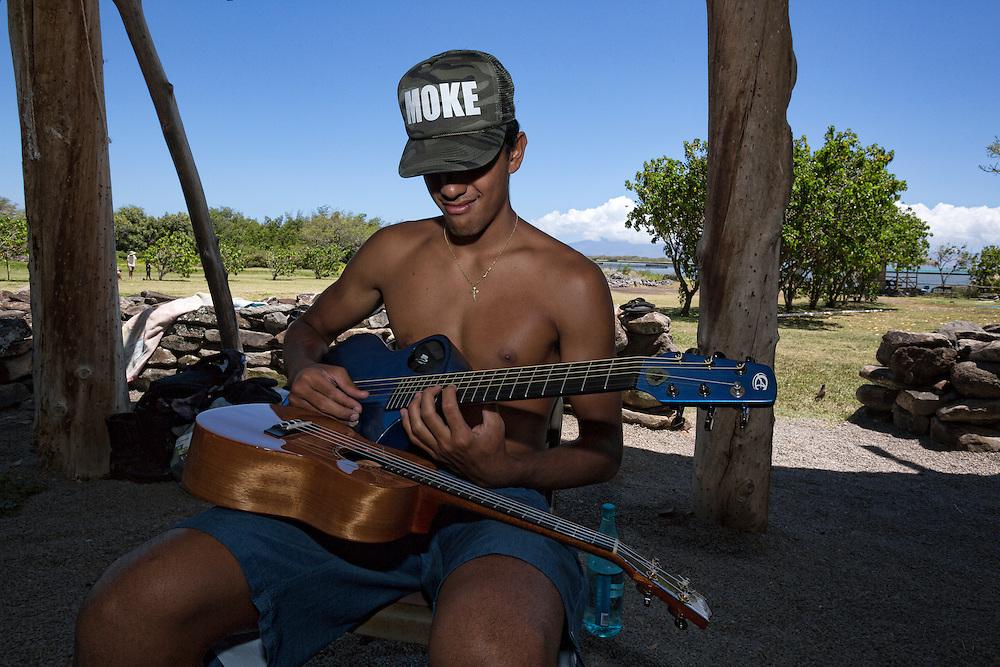 Kai Kahoaliki Fonseca plays guitar at the Keawanui Fishpond base camp.