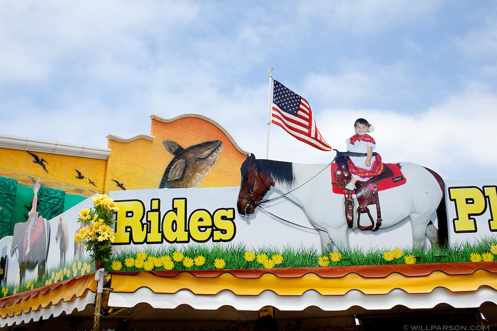 A pony ride booth is set up near an exhibition hall.