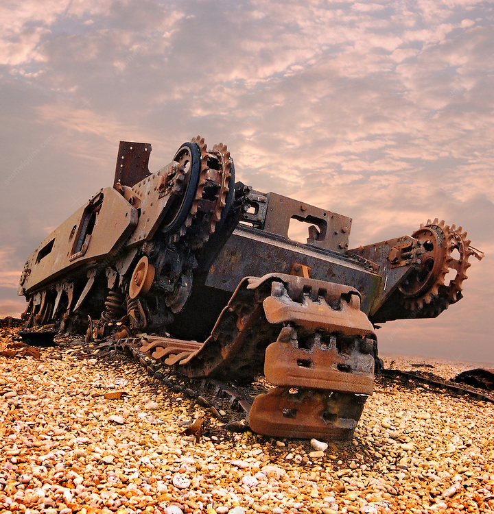 WWII vintage British Churchill tank destroyed by shell fire on shoreline stone beach in England