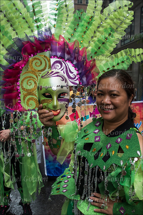 "Holding her traditional ""Masskara"" mask.  She is one of the many faces in the Philippine Independence Day Parade in NYC."