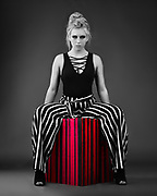 Selective color photo of model Brenna Smith in black and white striped pants sitting on red and black striped box.