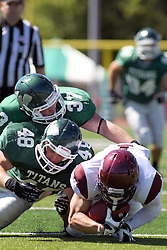08 September 2012:  Mike Heaton and Mike Kraft stop runner Michael Lenneman during an NCAA division 3 football game between the Alma Scots and the Illinois Wesleyan Titans which the Titans won 53 - 7 in Tucci Stadium on Wilder Field, Bloomington IL