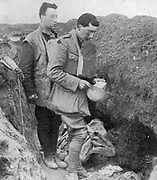World War I: Chaplain of the British regiment the lst Munsters saying a burial prayer over soldiers killed in their trench by a German shell. Near Cambrai, October 1918.