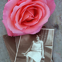 Vintage sepia studio photo of teenage girl or young woman seated in 1920s dress and with pink rose lying on top