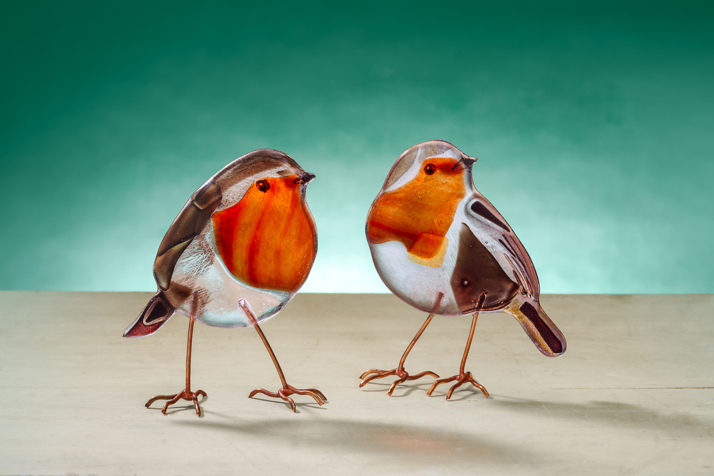Handmade glass birds, a pair of Robins, by artist Emma Butler-Cole Aiken,  who is based in the Scottish Borders. <br /> <br /> Emma is an architectural glass artist creating contemporary work using traditional materials. She has created around 75 commissioned works throught the UK.<br /> <br /> Emma is captivated by the colours, textures and exuberant beauty of glass. Seeking magical combinations of image and material, she strives to reach beyond the ordinary to create unique works which stand the test of time. Discerning when to allow a particular colour to shine out unhindered and when to bring control and distinction is a continuous process, the choices of possible outcomes almost overwhelming. In this creative process her faith and light emerge.