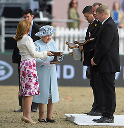 © Licensed to London News Pictures. 15/05/2016. Windsor, UK. HRH QUEEN ELIZABETH II presenting a trophy to the winning riders before an evening event held at the Royal Windsor Horse show to celebrate the 90th birthday of HRH Queen Elizabeth II. Acts from arounds the world have been invited to perform at the evening event, set in the grounds of Windsor Castle. Photo credit: Ben Cawthra/LNP