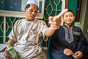 """11 JANUARY 2013 - BANGKOK, THAILAND:    A teacher talks to a student at a Muslim school in the Ban Krua neighborhood in Bangkok. The Ban Krua neighborhood of Bangkok is the oldest Muslim community in Bangkok. Ban Krua was originally settled by Cham Muslims from Cambodia and Vietnam who fought on the side of the Thai King Rama I. They were given a royal grant of land east of what was then the Thai capitol at the end of the 18th century in return for their military service. The Cham Muslims were originally weavers and what is known as """"Thai Silk"""" was developed by the people in Ban Krua. Several families in the neighborhood still weave in their homes.        PHOTO BY JACK KURTZ"""