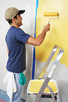 Man applying yellow paint to interior wall
