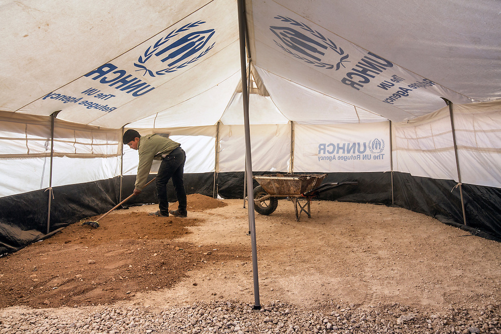 A young man prepares a tent for his family who are new residents in the camp. Jan. 31, 2014. Zaatari Camp, Jordan. (Photo by Gabriel Romero/Alexia Foundation ©2014)