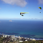 A hang glider and para glider fly high the hillside of Pedro Bonita high in the hills of Rio de Janeiro. Pilots of hang gliders and para gliders take tourists for tandem flights with breathtaking views of the city before landing on Sao Conrado beach. Rio de Janeiro,  Brazil. 9th September 2010. Photo Tim Clayton