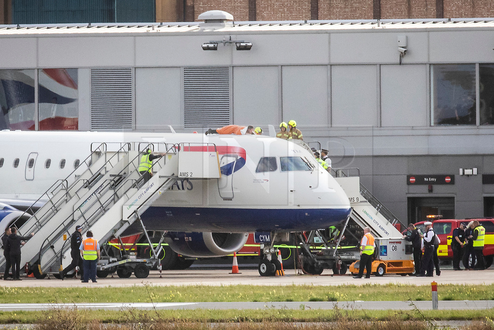 © Licensed to London News Pictures. 10/10/2019. London, UK. Emergency services try to remove an Extinction Rebellion protester on top of a British Airways plane at London City Airport. Protesters planned to occupy the terminal building in a 'Hong Kong-style' shutdown as part of ongoing protests calling on government departments to tackle the Climate Emergency. Photo credit: Rob Pinney/LNP