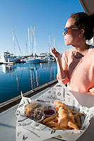 Taylor enjoys some fish and chips on the dock at Fisherman's Wharf on a summer's evening in Victoria, BC, Canada