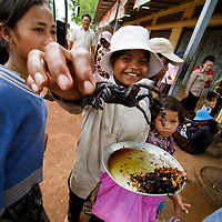 Young girl sells fried spider at bus stop, Skuon, Cambodia