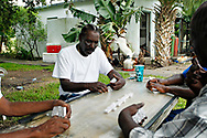 Retired sugar cane workers meet under an oak tree in the center of Miracle Village for their daily dominoes game. They keep their goats and chickens there, and have also populated the place with papaya, mango, avocado and banana trees. There are 52 duplexes in Miracle Village, or 104 units, about half of which are occupied by registered sex offenders, the other half by the retired sugar cane workers -- living together harmoniously and self sufficiently. Miracle Village residents do all their own yard work and landscaping, maintain a wastewater treatment facility and grow their own food. MELISSA LYTTLE   |   Times (07/19/13 Pahokee, Fla.)