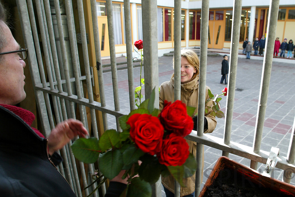 ROTTERDAM - NETHERLANDS - 06 MARTS 2006 -- Social Democrats campaigning from door to door at the Sint-Mariastraat. The leader Peter van HEEMST hands over a red rose to a teacher of the local school where there is a lot of immigrant children. PHOTO: ERIK LUNTANG /