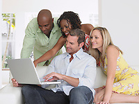 Four adults on sofa looking at laptop