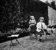 Two young French girls play in a garden. Circa 1900