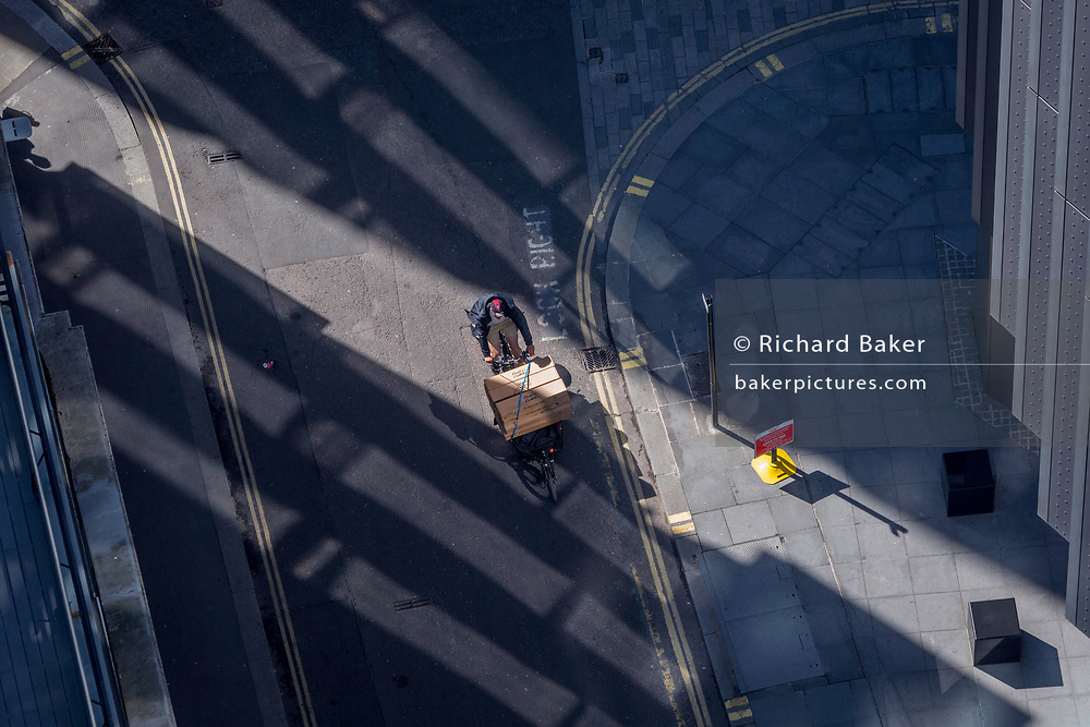 Looking down from an aerial view towards small business figures walking through blue reflected light in the City of London, the capital's ancient financial district, on 13th May, in London, England.