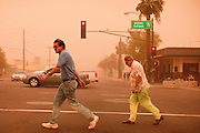 "18 AUGUST 2011 - PHOENIX, AZ:  People cross a street during a ""haboob"" in Phoenix Thursday. A haboob (Arabic for ""strong wind"") is a type of intense duststorm commonly observed in arid regions throughout the world. They have been observed in the Sahara desert, the Arabian Peninsula, throughout Kuwait, and most arid regions of Iraq. In the USA, they are frequently observed in the deserts of Arizona, including Yuma and Phoenix, as well as New Mexico and Texas. ""Haboob"" has been widely used to describe dust storms for more than a generation In Arizona but this year the very word ""haboob"" has become a political football because some conservatives have lobbied against use of the word, favoring English words, like ""dust storm.""       PHOTO BY JACK KURTZ"