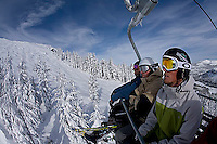 Three young men riding chairlift at Kirkwood ski resort near Lake Tahoe, CA.