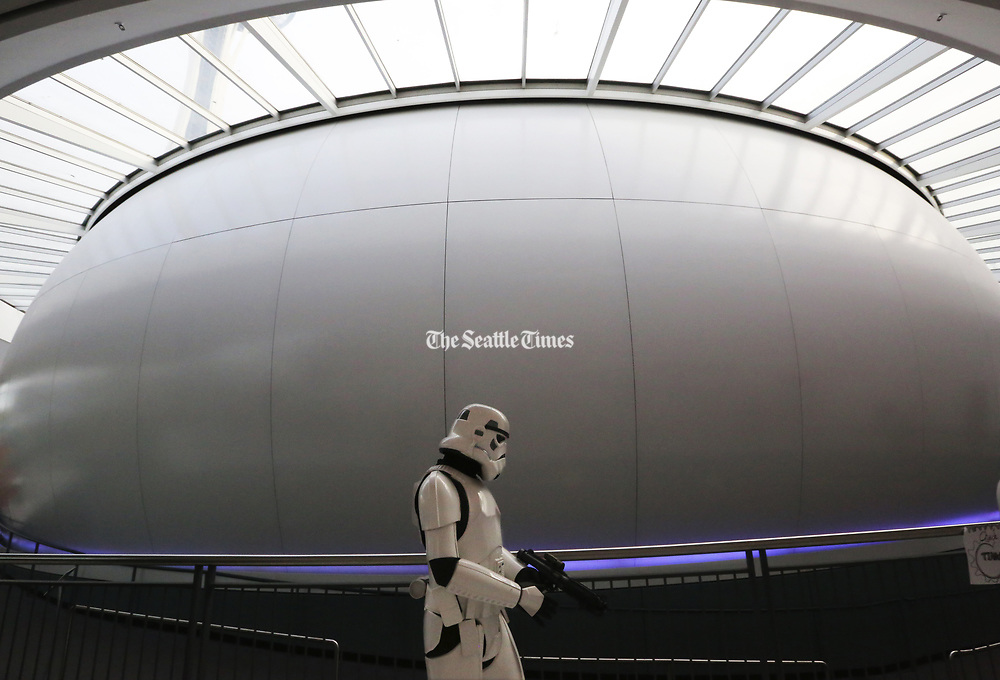 A Stormtrooper from the local 501st Legion passes the IMAX Theatre at the Pacific Science Center after visiting with movie-goers waiting for Rogue One: A Star Wars Story opening. (Alan Berner / The Seattle Times)