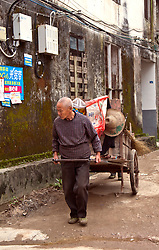 Old Chinese man pulling cart on a small street near the River Li in Yangshuo. Humans often do the work of animals and machines even in today's highly industrialized China.