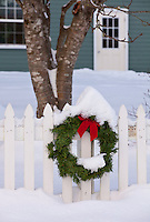 Snow-covered Christmas wreath on white picket fence lit by soft morning light, tree and building in background, Kodiak, Alaska
