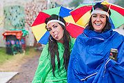 As usual, the rain begins to fall and fails to dampen spiriits. The 2014 Glastonbury Festival, Worthy Farm, Glastonbury. 26 June 2013.