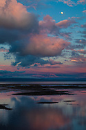 The moon rises over the San Francisco Bay at sunset.  A passing storm has cleansed the air, Foster City, California.