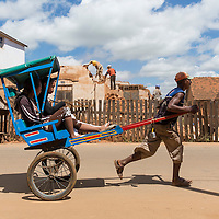 Madagascar, Ambositra, Man runs while pulling Pousse Pousse taxi cart with pasengers past demolished house on downtown street