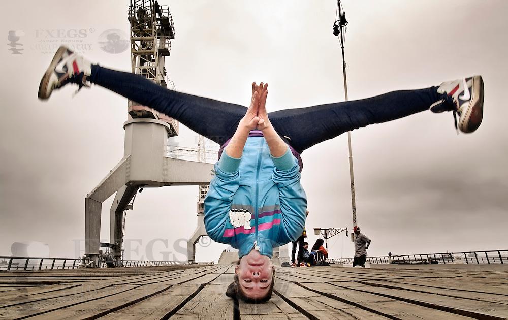 Retrato de mujer joven en postura de breakdance en el muelle Barón de Valparaíso, Chile.