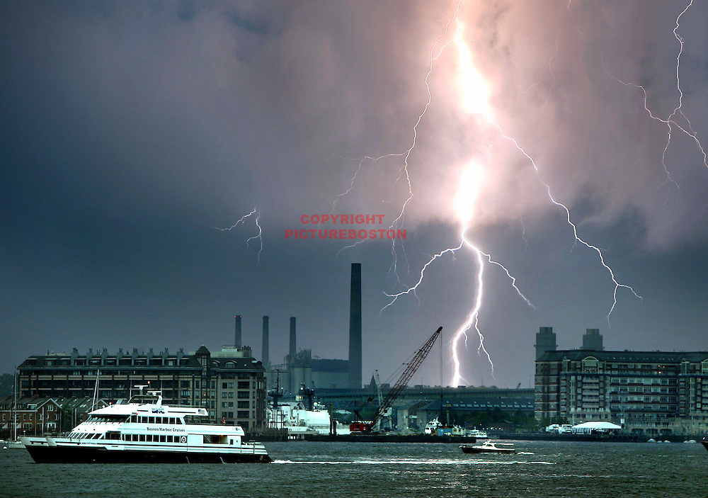 "(07/11/06-Boston,MA) Boats make a ""b-line"" for port as lightning from a series of intense thunderstorms strikes over and beyond Charlestown and Everett. Several cities and towns reported house fires due to lightning strikes and there was a report of a funnel cloud over Hampton Beach,NH.(071106lightningmg-Staff Photo:Mark Garfinkel.saved phto6/wed)"