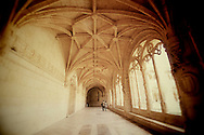 A couple walks through the romantic cloister of Jerónimos Monastery a UNESCO World Heritage Site, in Lisbon, Portugal