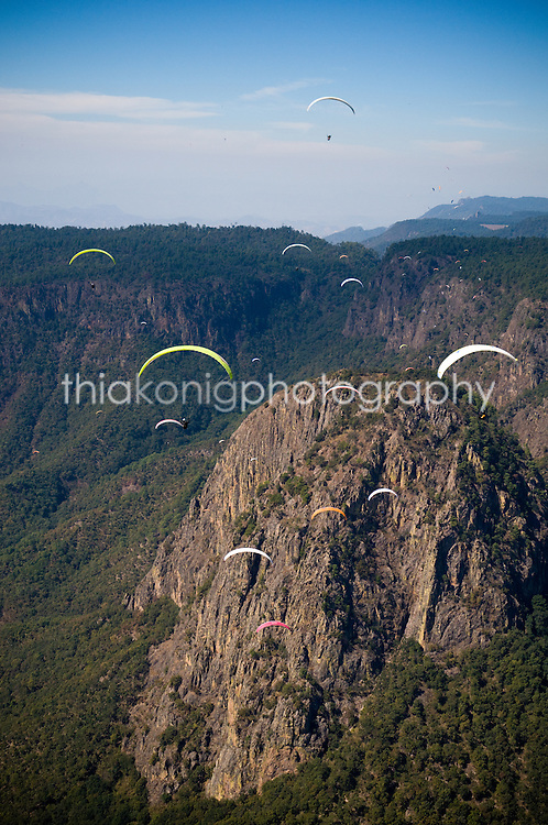 Paragliders fly towards the Pinon, at Valle De Bravo, Mexico