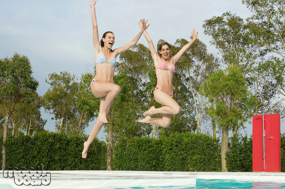 Young Women Jumping into Swimming Pool