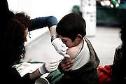 ROMA. MEDICO DELLA CROSE ROSSA INIETTA IL VACCINO A UN BAMBINO DEL CAMPO NOMADI CASILINO 900 DI ROMA