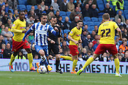 Brighton's Beram Kayal runs past Odion Ighalo during the Sky Bet Championship match between Brighton and Hove Albion and Watford at the American Express Community Stadium, Brighton and Hove, England on 25 April 2015. Photo by Geoff Penn.
