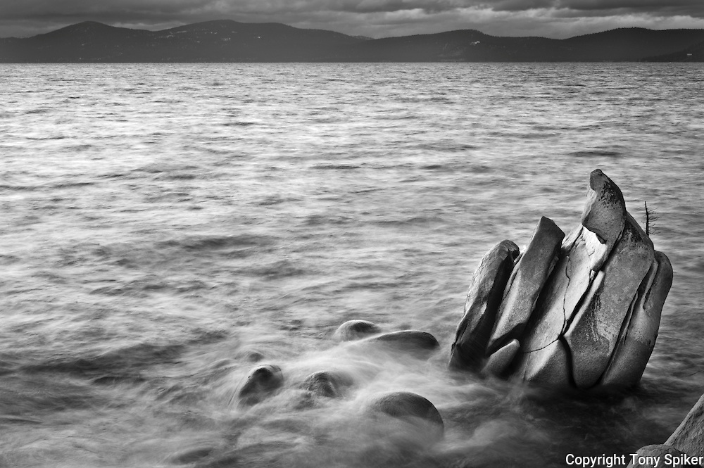 """""""Lake Tahoe Boulders 3"""" - A black and white photograph of waves pounding on an outcropping of rocks on the Eastern Shore of Lake Tahoe"""
